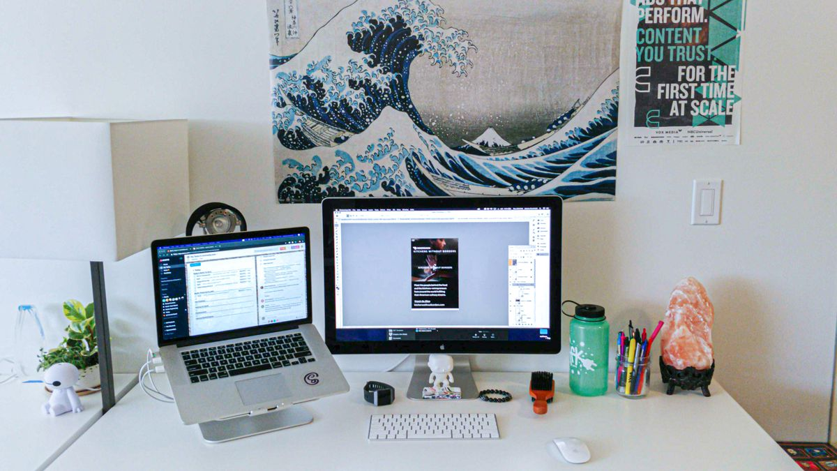 Alesha's Desk with a salt lamp, water bottle, jar of pens and pencils, and a Hokusai poster on the wall behind.