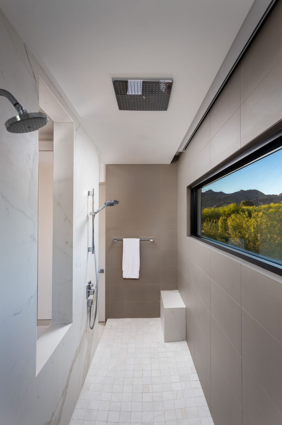 A bathroom with a shower and rectangular window with desert landscape views.