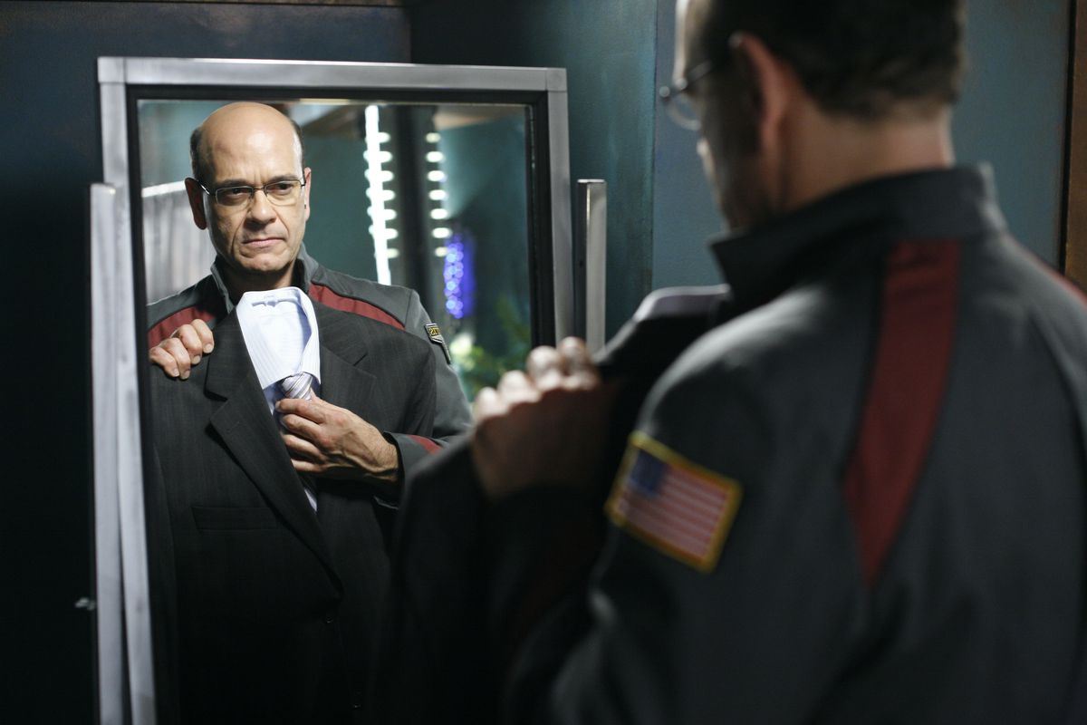 Robert Picardo on Stargate Atlantis holding a suit up in front of a mirror