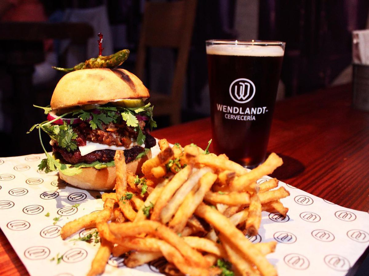 A tall sandwich overloaded with meat and fixings, sits on branded waxpaper with a pile of garnished fries beside a pint of dark beer