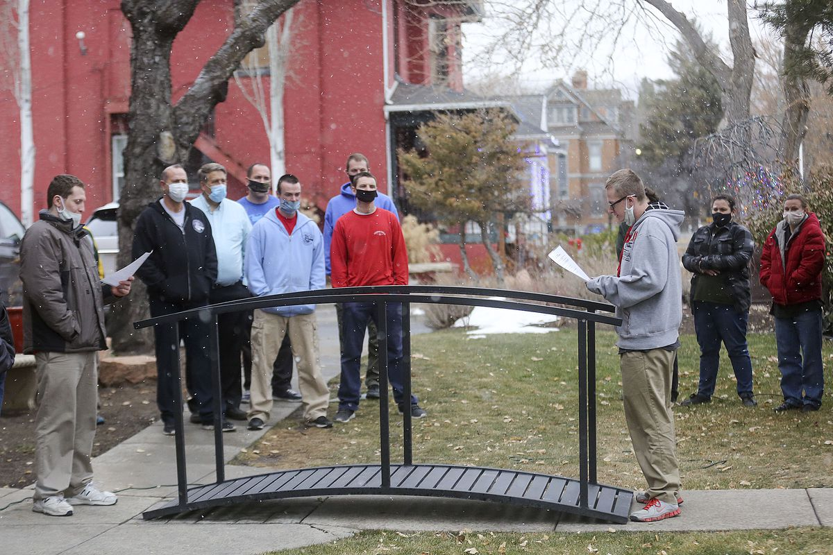 """Tristan Searle, left, and Dylan Vantassell, right, participate in a """"crossing over"""" ceremony in front of The Other Side Academy in Salt Lake City on Thursday, Dec. 17, 2020. During the ceremony, Vantassell asked to be admitted and promised to commit to accountability, self-reliance, humility, honesty and growth before walking over the bridge. The academy is a 2 1/2 year residential program where those who have been involved in the criminal justice system can learn social, vocational and life skills. A $100,000 donation from businessmen David Ibarra and K.O. Murdock will help expand the program and remodel a former senior living center that is next door to the academy."""