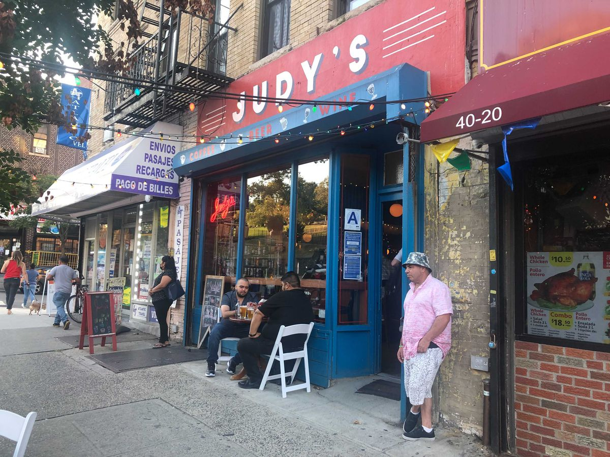 A red and blue bar storefront with two people sitting out front on white chairs sipping beer and a person in a pink shirt near the entrance to the bar.