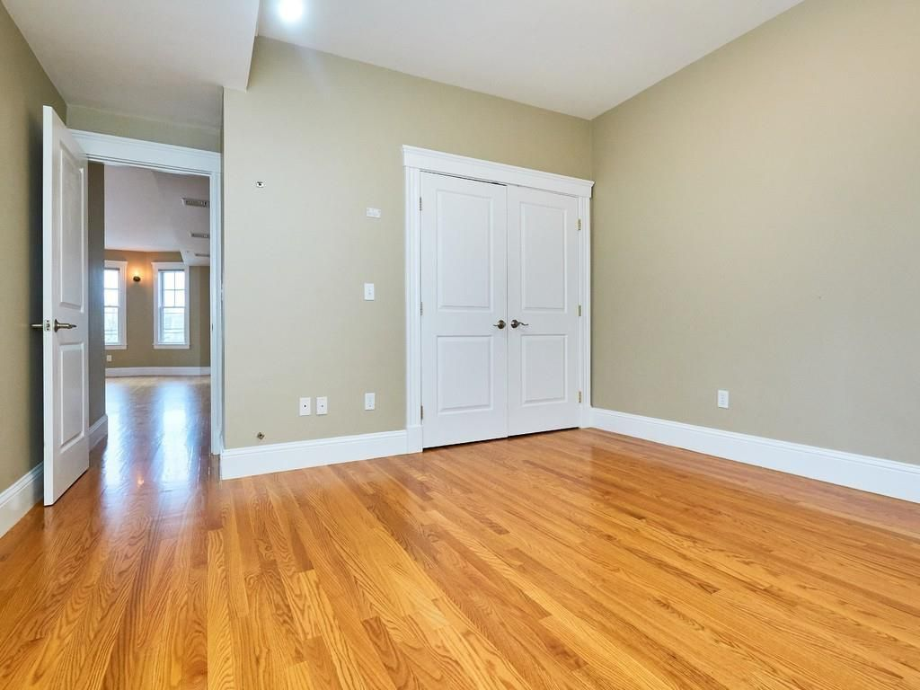 An empty bedroom with a closed set of closet doors.