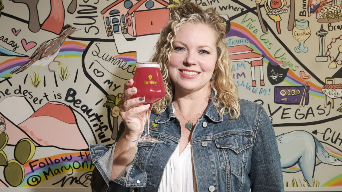 A woman stands in front of a mural holding a beer