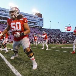 Utah Utes offensive lineman Orlando Umana (50) jumps off the line after snapping the ball to Utah Utes quarterback Tyler Huntley (1) during warmups before the start of an NCAA football game between the Utah Utes and Colorado Buffaloes at Rice-Eccles Stadium in Salt Lake City on Saturday, Nov. 30, 2019.