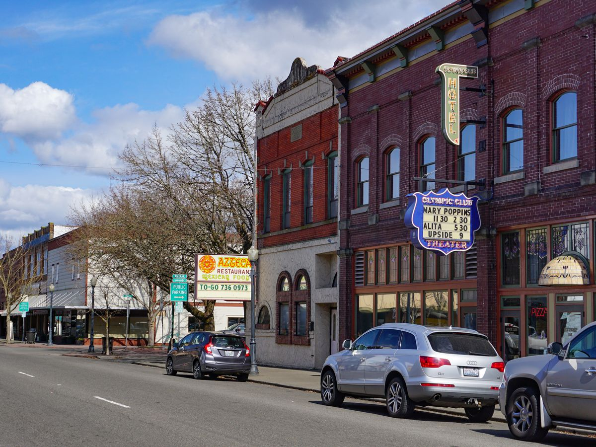 Short brick buildings from one to three stories line a paved arterial street.