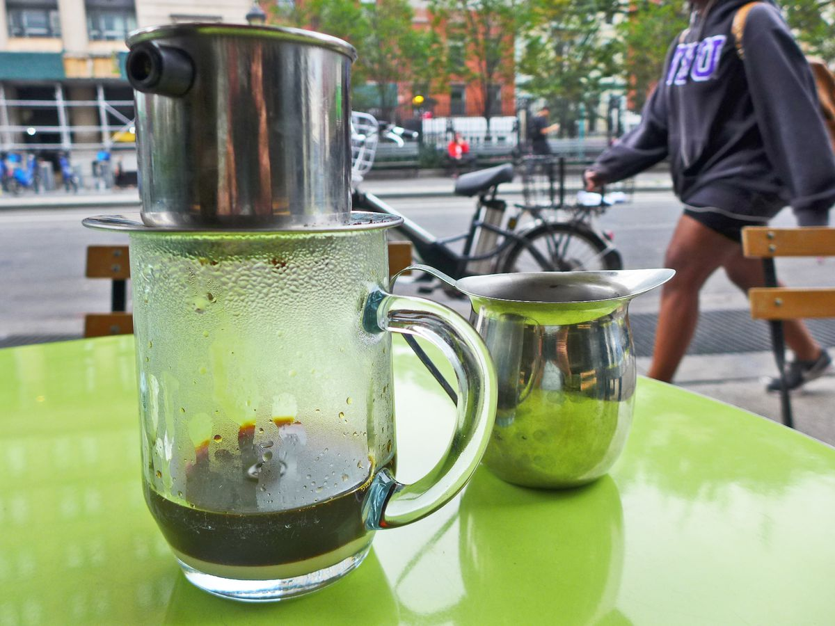 A clear glass mug with coffee dripping into it from a metal contraption on top.