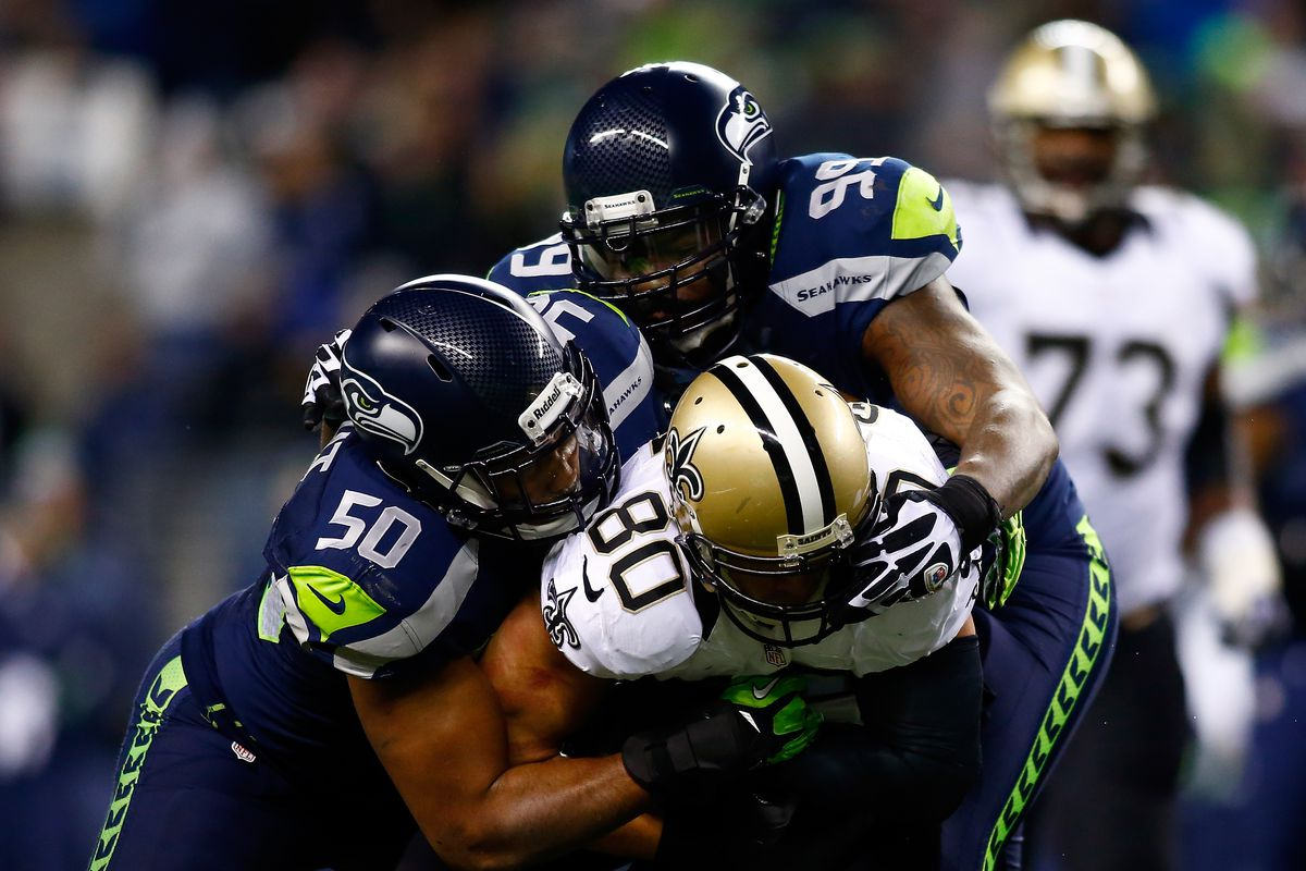 SEATTLE, WA - New Orleans Saints tight end Jimmy Graham (80) is tackled by Seattle Seahawks defensive tackle Tony McDaniel (99) and linebacker K.J. Wright (50) at CenturyLink Field.