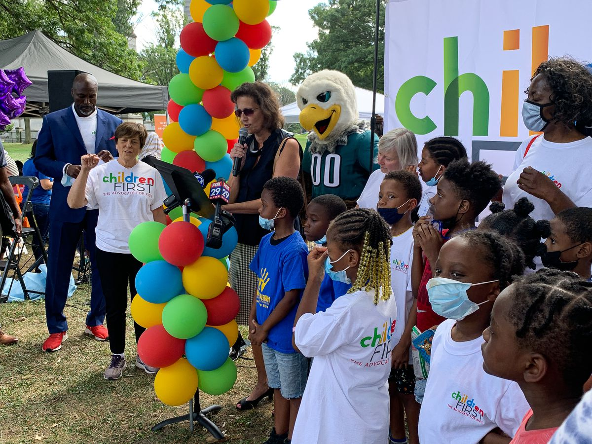 Annette Myarick of the PA chapter of the American Association of Pediatrics, speaks at a Children First event surrounded by several children and the Philadelphia Eagles mascot behind her.