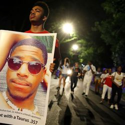 Marchers carried signs with pictures of victims of gun violence.| Scott Olson/Getty Images