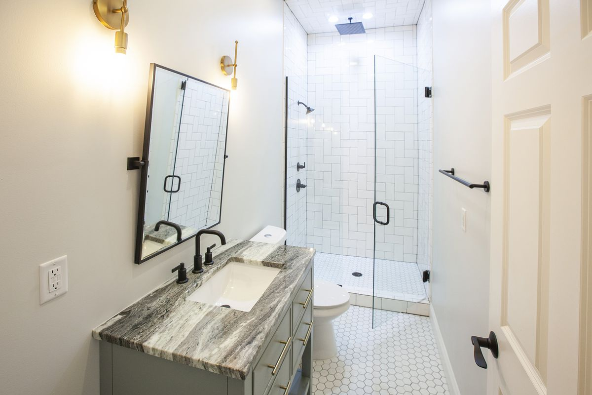 A bathroom with white walls and white tiled floor. The glass shower has larger subway tiles.