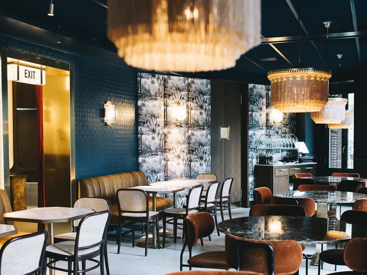 A cafe interior with dark blue paint, gold accents, warm pendant lighting, and tufted brown leather banquets