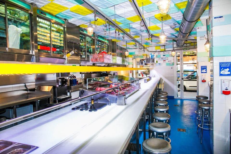 An energetic interior with a bright white bar, light blue and yellow accents on the ceiling, royal blue floor, and stools at the counter.