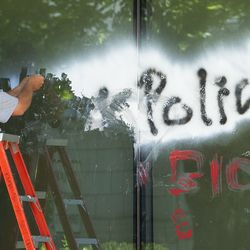 Branden Woolley scrapes paint from a window at the Salt Lake County District Attorney's Officebuilding in Salt Lake City on Friday, July 10, 2020. The building suffered tens of thousands of dollars in damage when protesters broke out at least three windows and spread red paint over large portions of the building and area in front of the structure on Thursday.