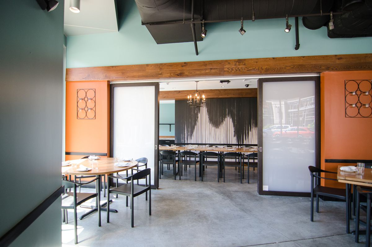 Inside a restaurant, sliding doors open to reveal a private dining room with black-and-white-striped wallpaper and a long table. There are light blue and orange accents.