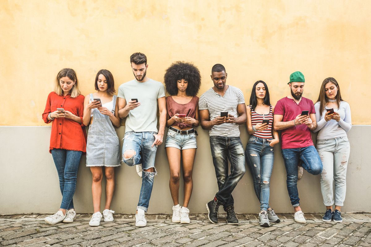 Multiracial friends using smartphones stand against a wall.