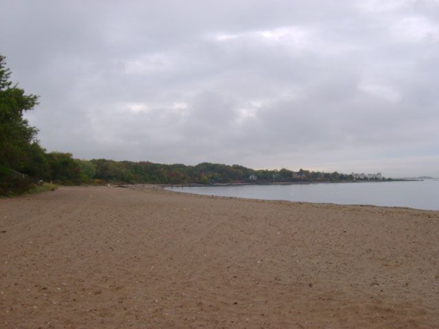 In the foreground is a beach. There is a body of water and trees in the distance.