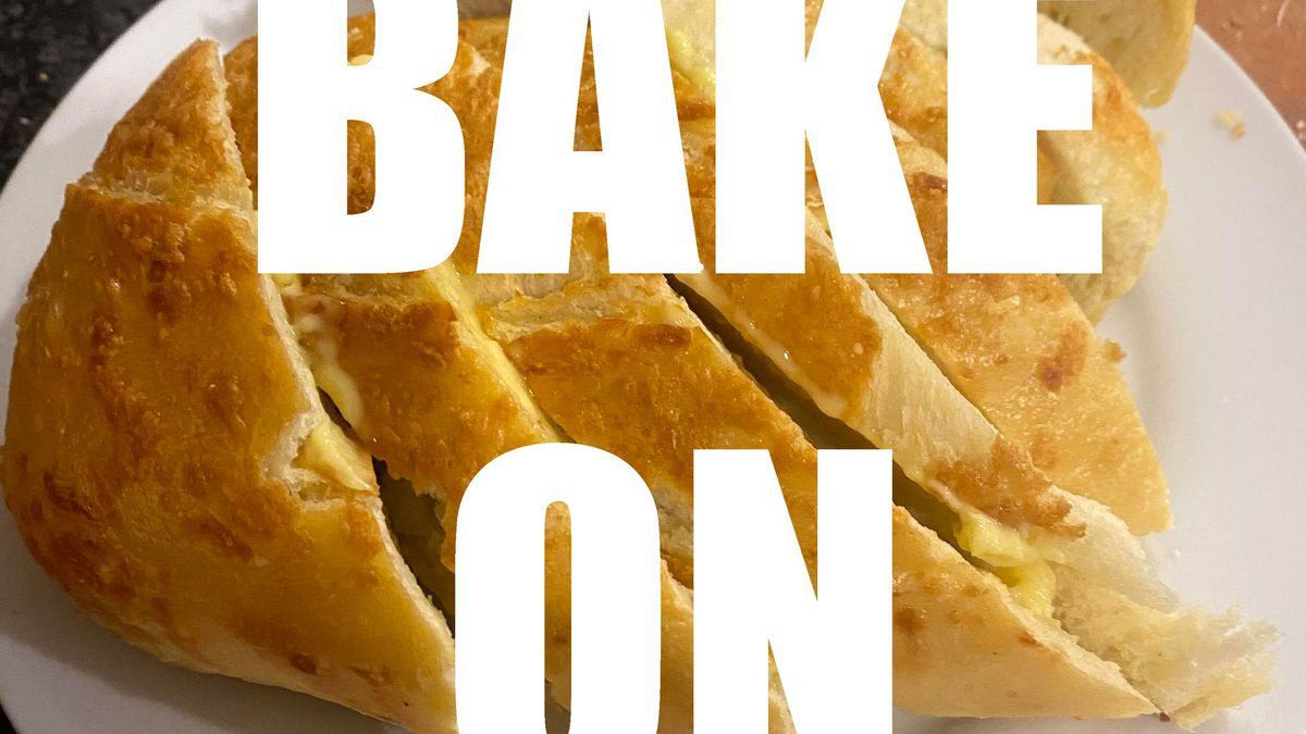 """White all-caps text reads"""" BAKE ON"""", superimposed over a photo of sliced bread."""