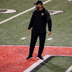 Utah Utes head coach Kyle Whittingham stands on the field as his team warms up before the game between the Utah Utes and the USC Trojans at Rice-Eccles Stadium in Salt Lake City on Saturday, Nov. 21, 2020.