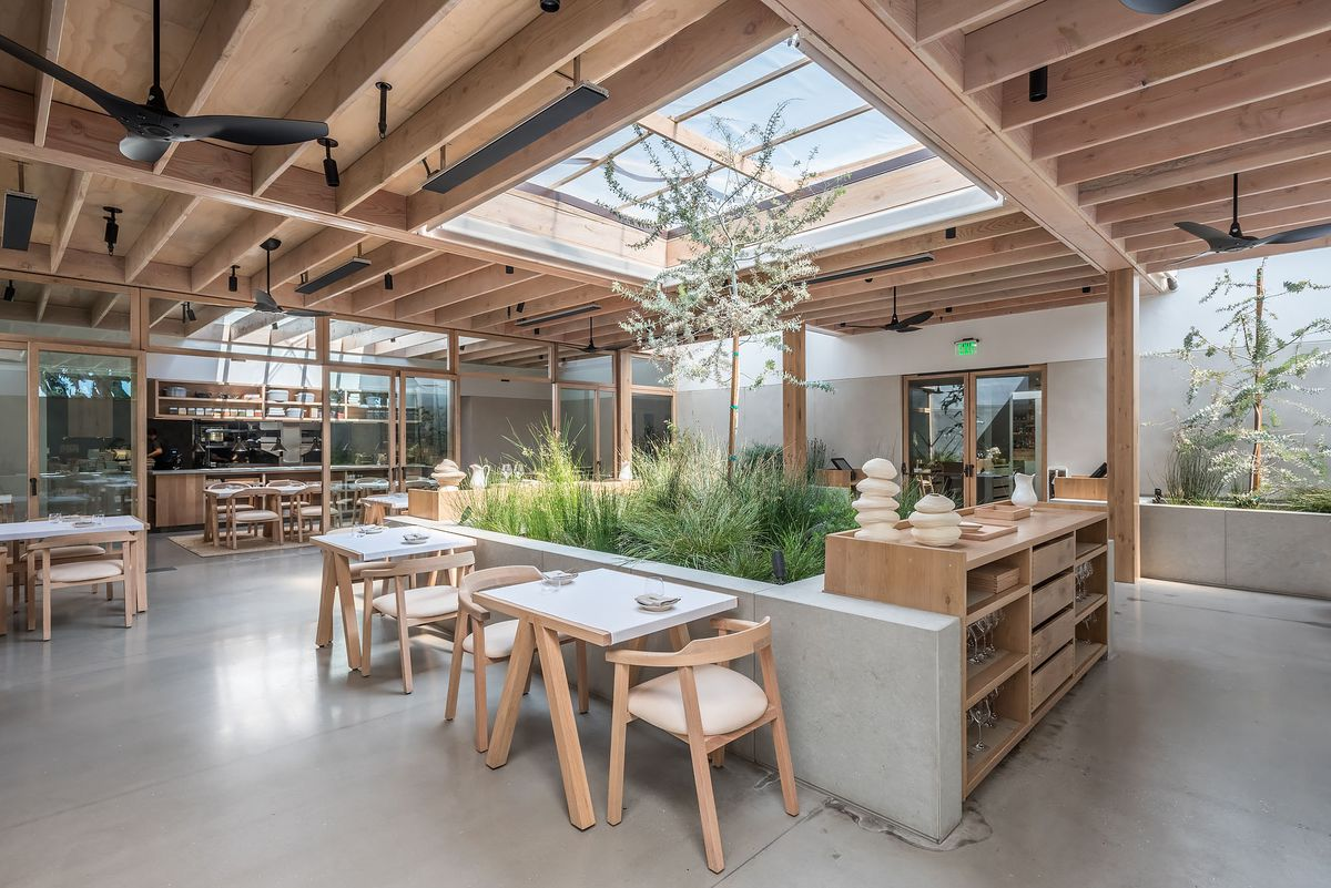 Dining room inside Auburn with skylight, wooden rafters, and grey concrete floors with foliage.