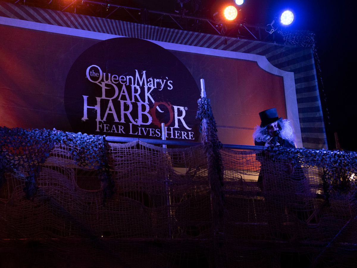 The exterior of a haunted house. There is a sign that reads: Queen Mary's Dark Harbor.