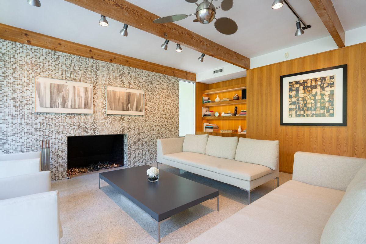 A living room has white leather couches, a black coffee table, and a fireplace.