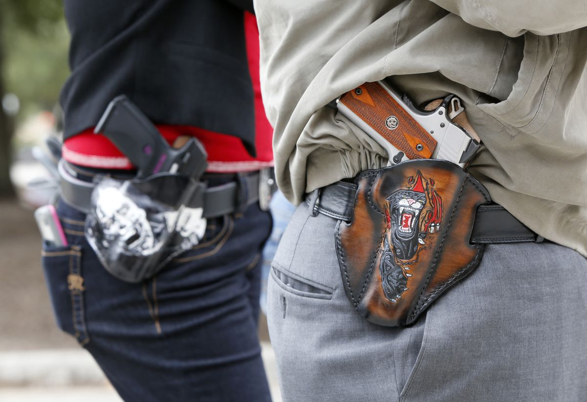 Two people sporting firearms in hip holsters
