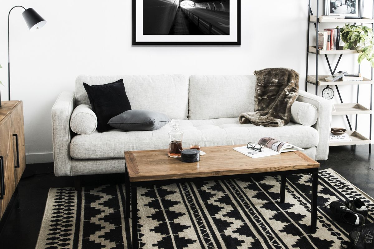 Living room with black and white patterned rug, beige sofa, and wood and metal coffee table.