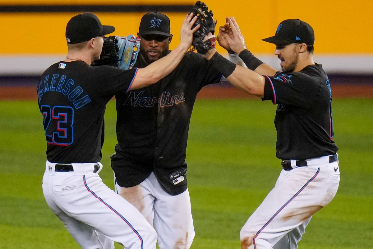 Corey Dickerson #23, and Starling Marte #6, and Adam Duvall #14 of the Miami Marlins celebrate the win against the Atlanta Braves by score of 4-2 at loanDepot park