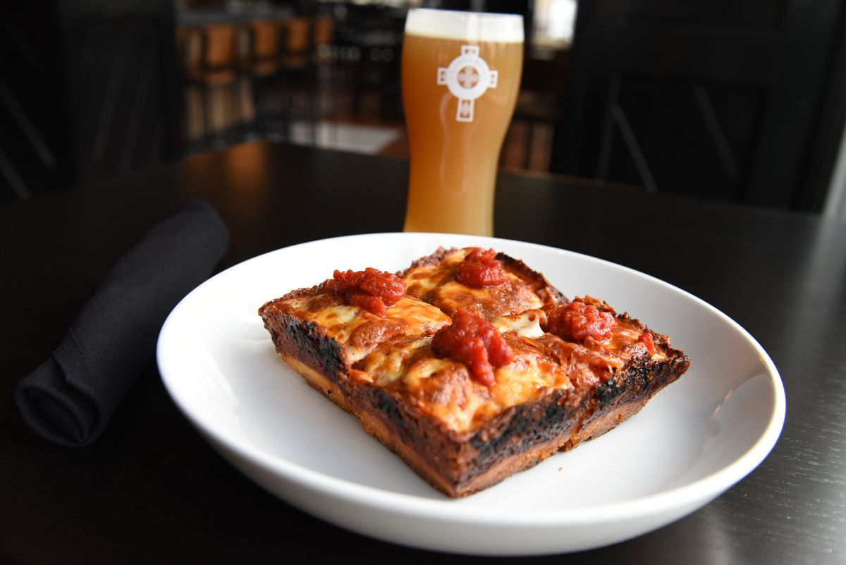A personal-sized square of Detroit-style pizza sits on a white plate on a dark table. A glass full of beer is visible in the background.