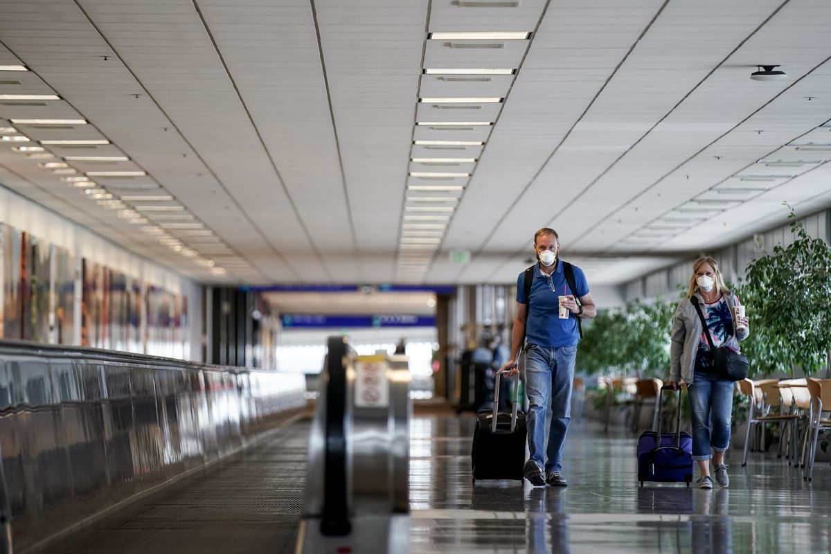 Siblings Robert Olson, of Farmington, and Carole Larson, of Logan, walk through Terminal 1 at Salt Lake City International Airport as they travel to Dallas on Thursday, April 30, 2020. Like airports all over the world, Salt Lake's airport has seen air traffic plummet due to the COVID-19 pandemic.