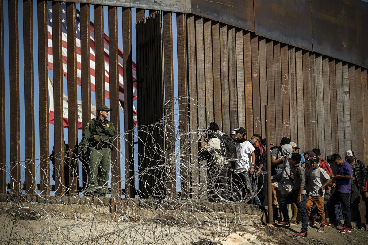 Central American migrants look through a border fence as a US Border Partol agents stands guard near the El Chaparral border crossing in Tijuana, Baja California State, Mexico, on November 25, 2018.