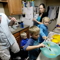 Kelly Burton tastes the pumpkin while making pumpkin pie from scratch as 3-year-old Logan scoops it out with brother Porter (6) and sister Mykenzie (8) on Sept. 25. Mary looks on with 2-month-old Raiger.