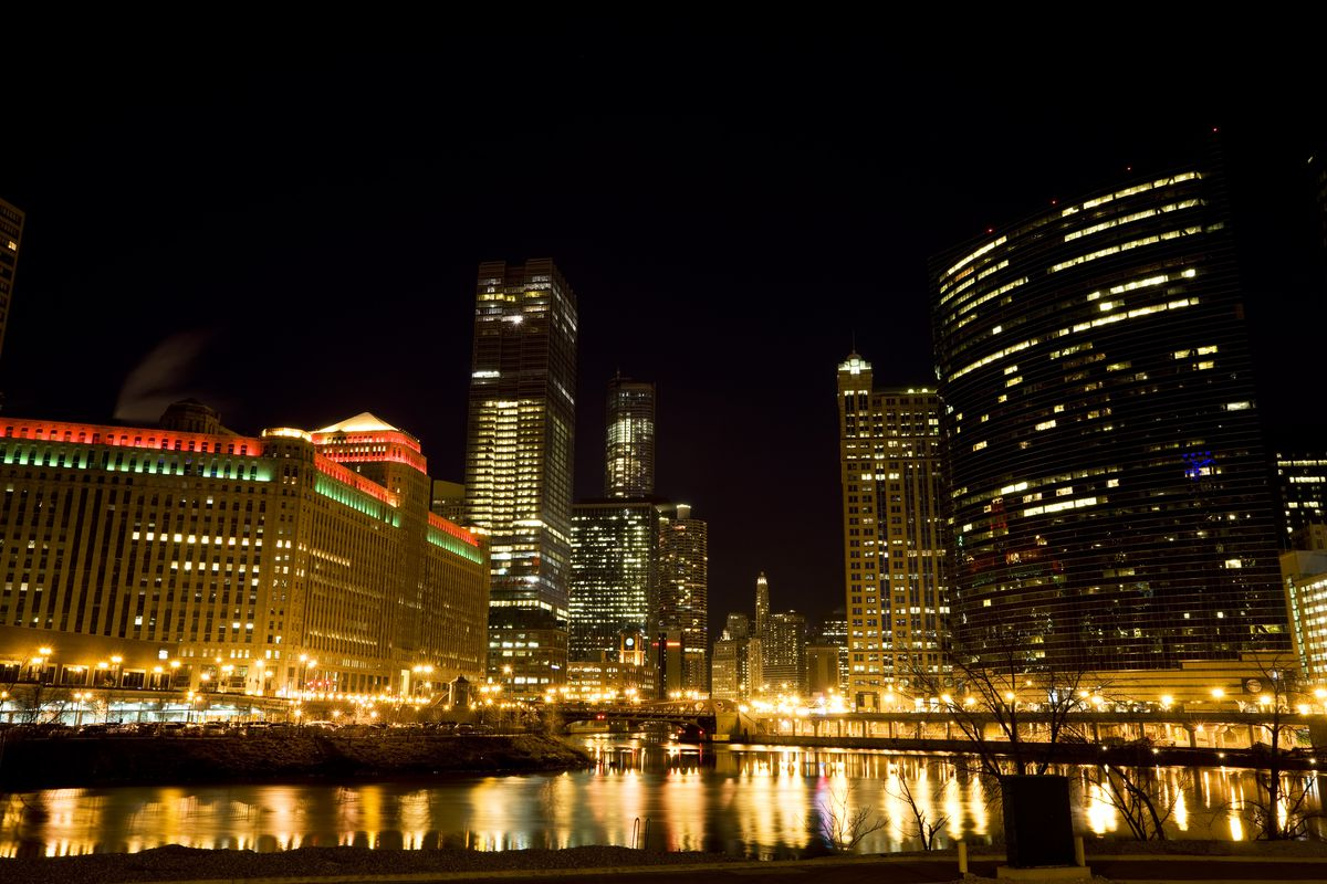 From across the river, a night time cityscape shows several buildings.