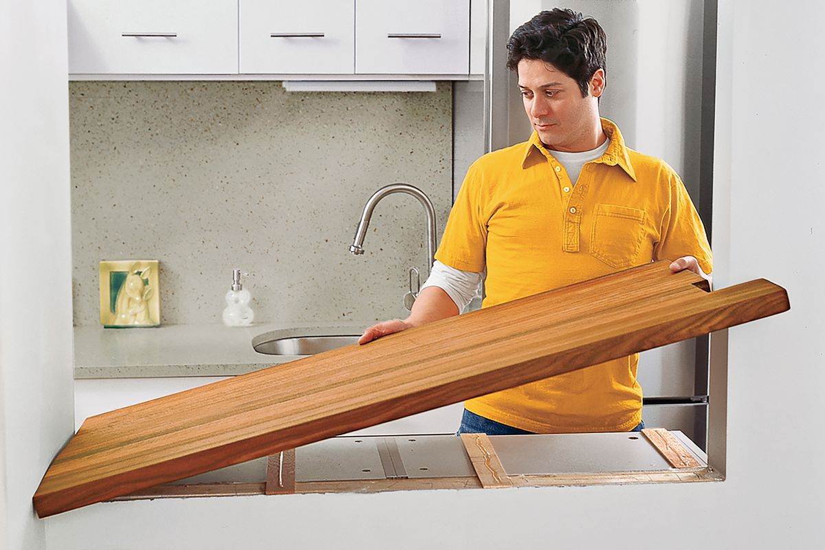 Man installing wood countertop in kitchen.