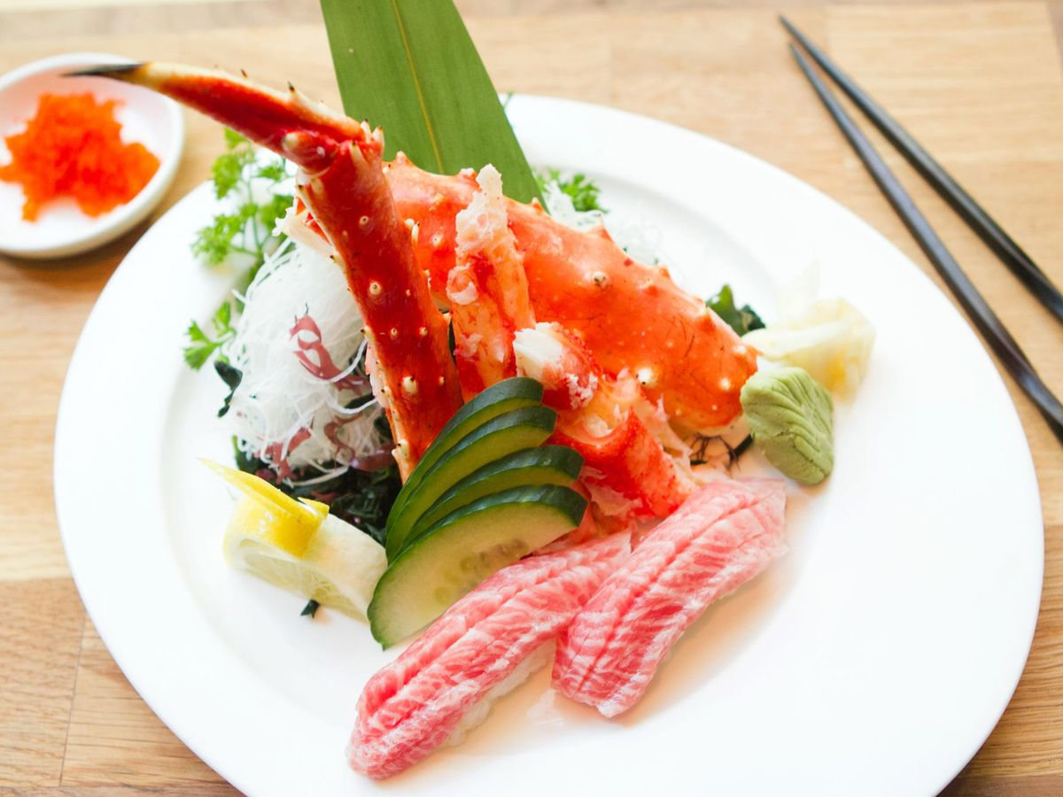 Crab legs and pieces of sushi and sashimi sit on a white plate on a light wooden surface, with black chopsticks to the side