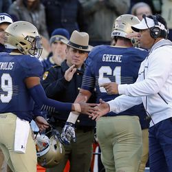 Navy head coach Ken Niumatalolo, right, greets quarterback Keenan Reynolds (19) after Reynolds scored a touchdown to break the NCAA all-time rushing touchdown record in the first half of an NCAA college football game against SMU, Saturday, Nov. 14, 2015, in Annapolis, Md.