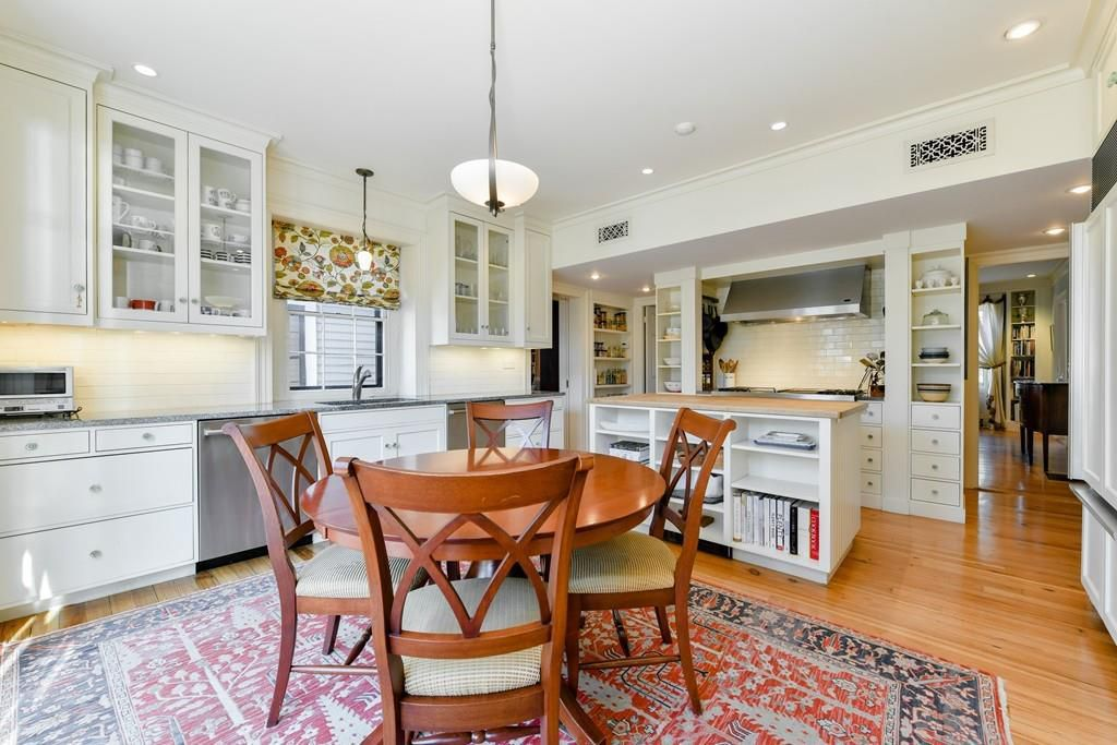 A large kitchen with a table and chairs and lots of shelving and cabinetry.