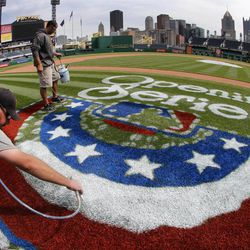 In this photo taken with a fisheye lens, workers Matt Gerhardt, left, and Nick Gialloreto paint the opening day logo along the third baseline of PNC Park in preparation for the Pittsburgh Pirates home-opener, Tuesday, April 3, 2012, in Pittsburgh. The Pirates open the baseball season Thursday, April 5, against the Philadelphia Phillies.