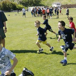 Utah State University football coach Matt Wells watches his son Wyatt and other kids during a kids football camp in Logan Friday, June 12, 2015.