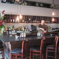 """Bar manager Chris Burgeson makes a drink at the 10-seat bar up front. """"Benjamin Franklin-style"""" bulbs swing overhead."""