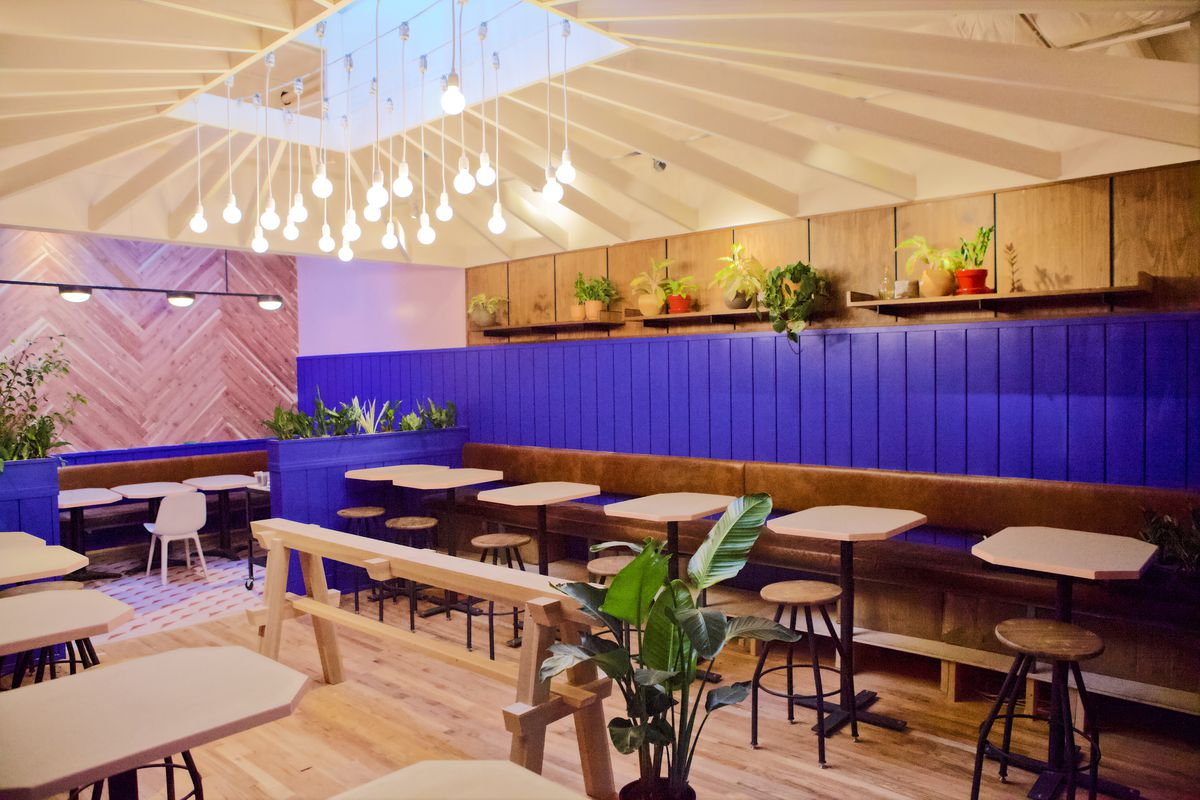 Hunky Dory's dining room has hanging string lights in the middle, a purple wall in the back, and a wood wall to the left.