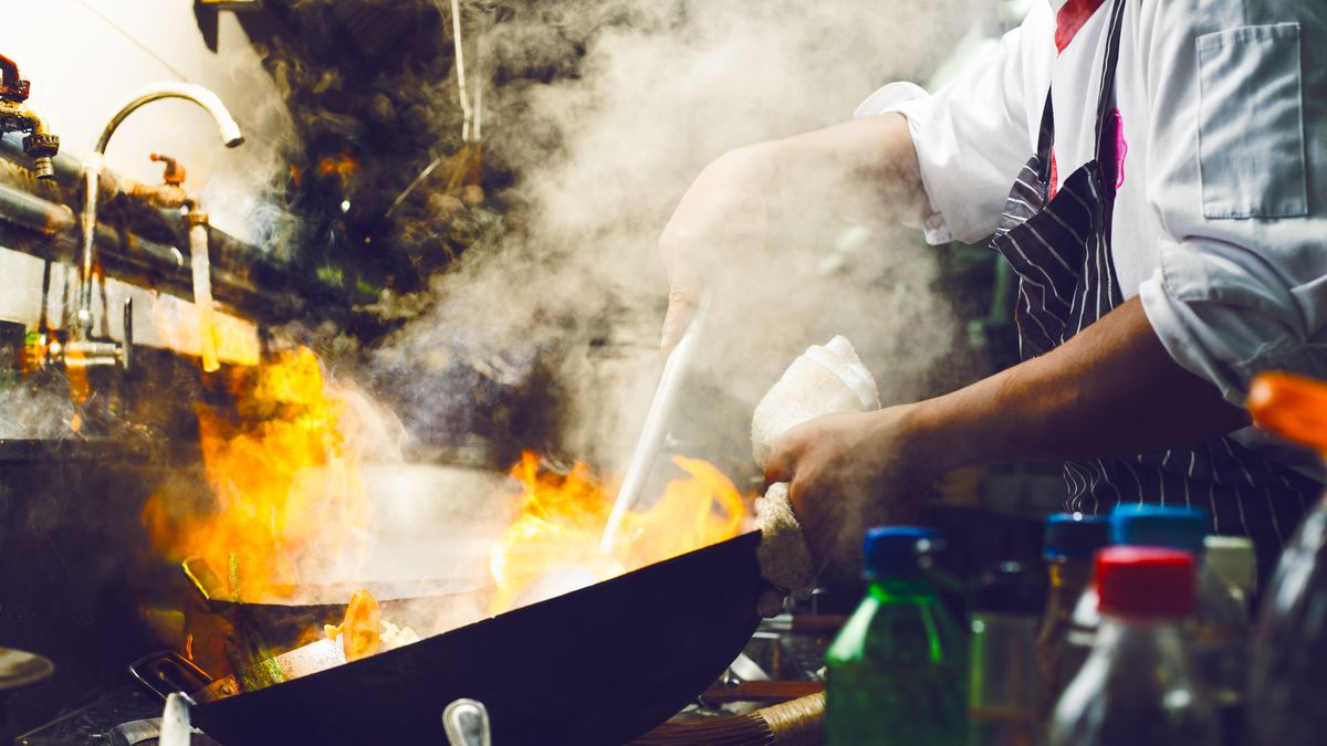 Chef stirs a work that's on fire.