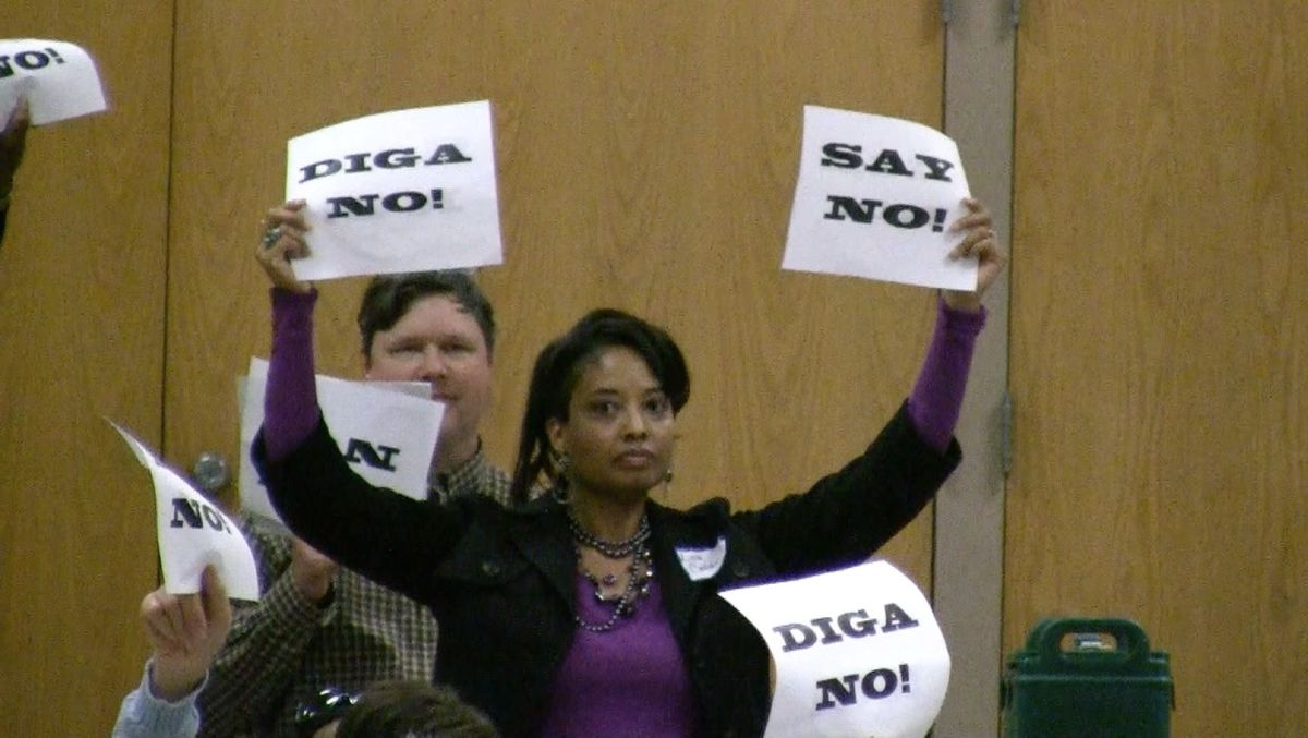 Lisa Calderon holds up signs Tuesday showing her opposition to the proposed reform plan in Far Northeast Denver.