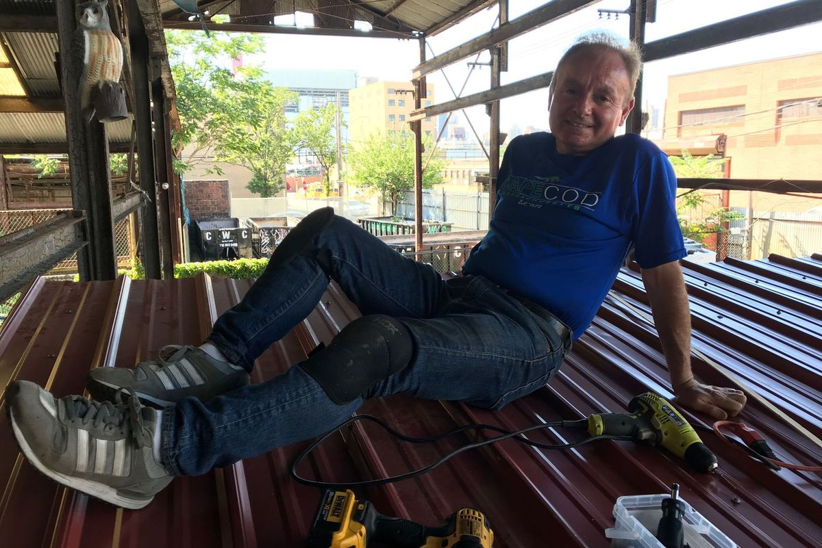 Tom Saat sits atop the roof of tiny house he built.