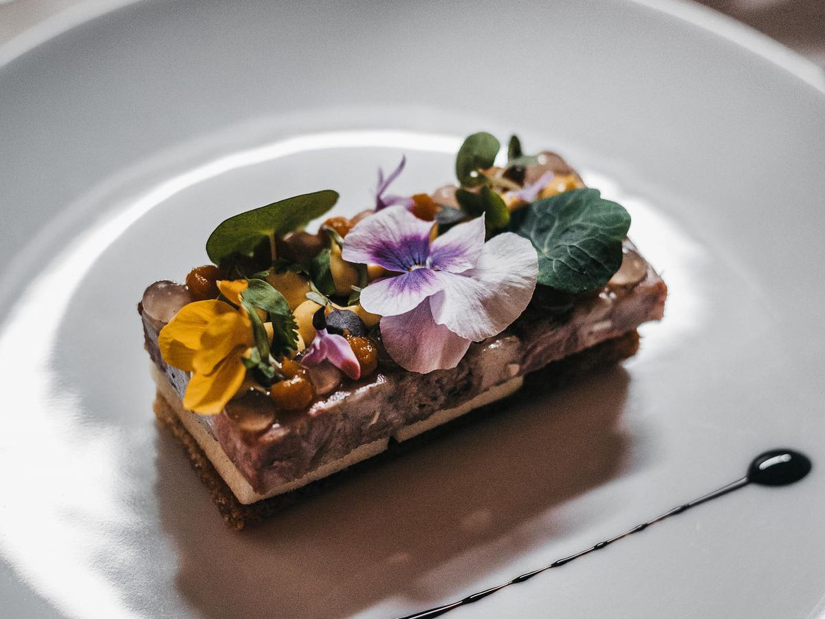 A thick rectangle of terrine topped with chopped nuts and flowers sits on a white plate parallel to a long, thin streak of sauce