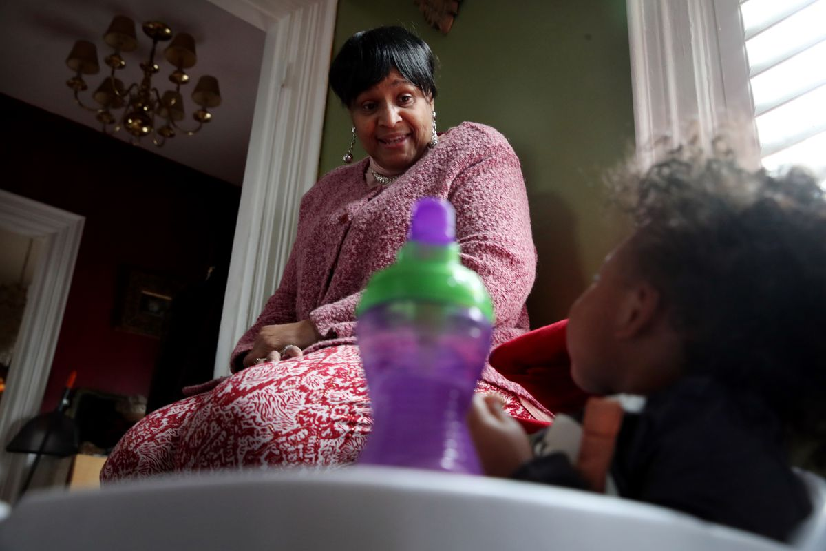 A child care provider looks down at a baby in a baby chair.
