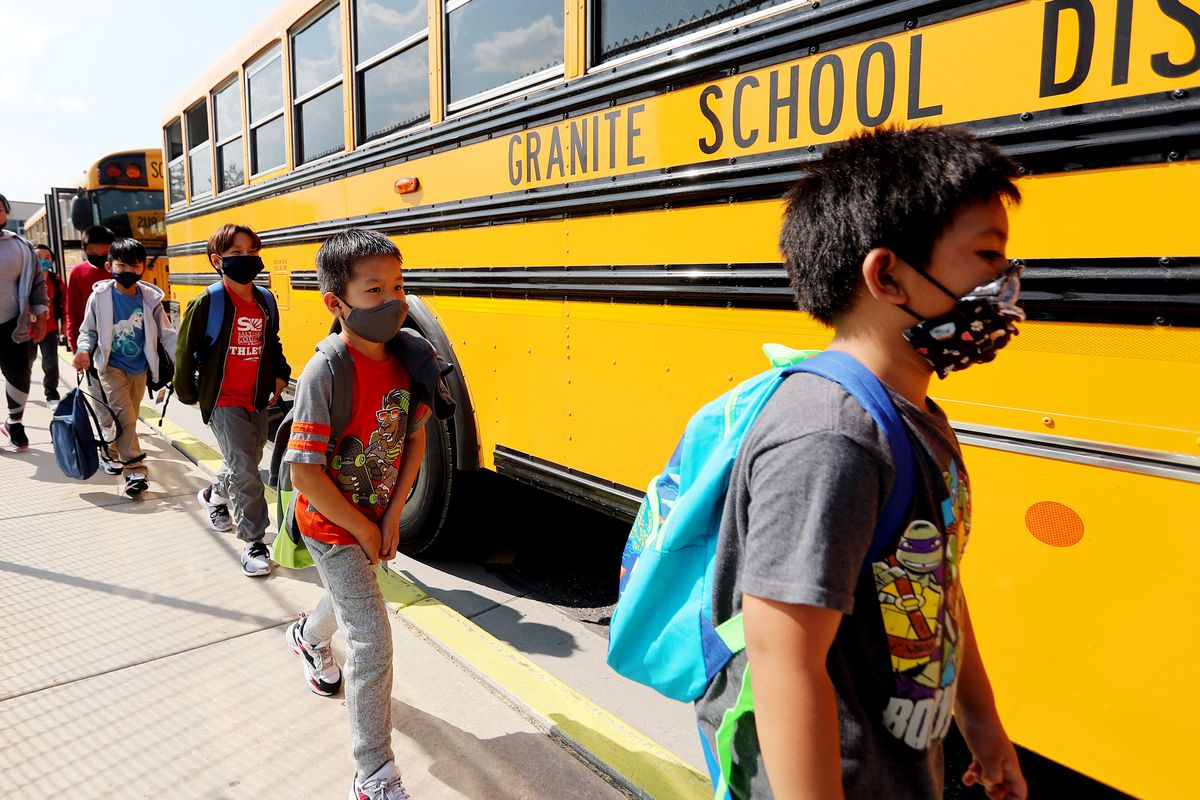 Elementary school students in South Salt Lake get on the bus with masks on.