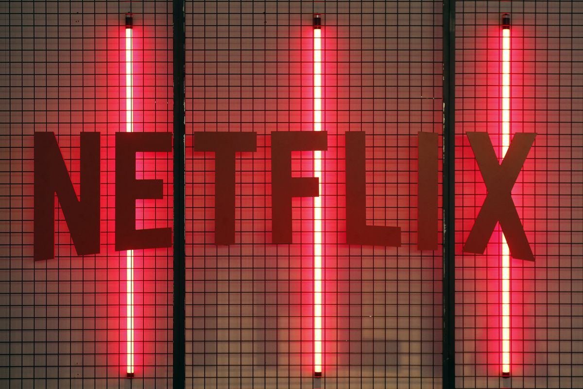 The Netflix logo with three red neon lights behind it.