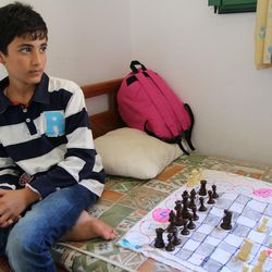 A Syrian boy plays chess with his sister on a makeshift board at the Kyllini refugee camp in Myrsini, Greece, July 11, 2016.